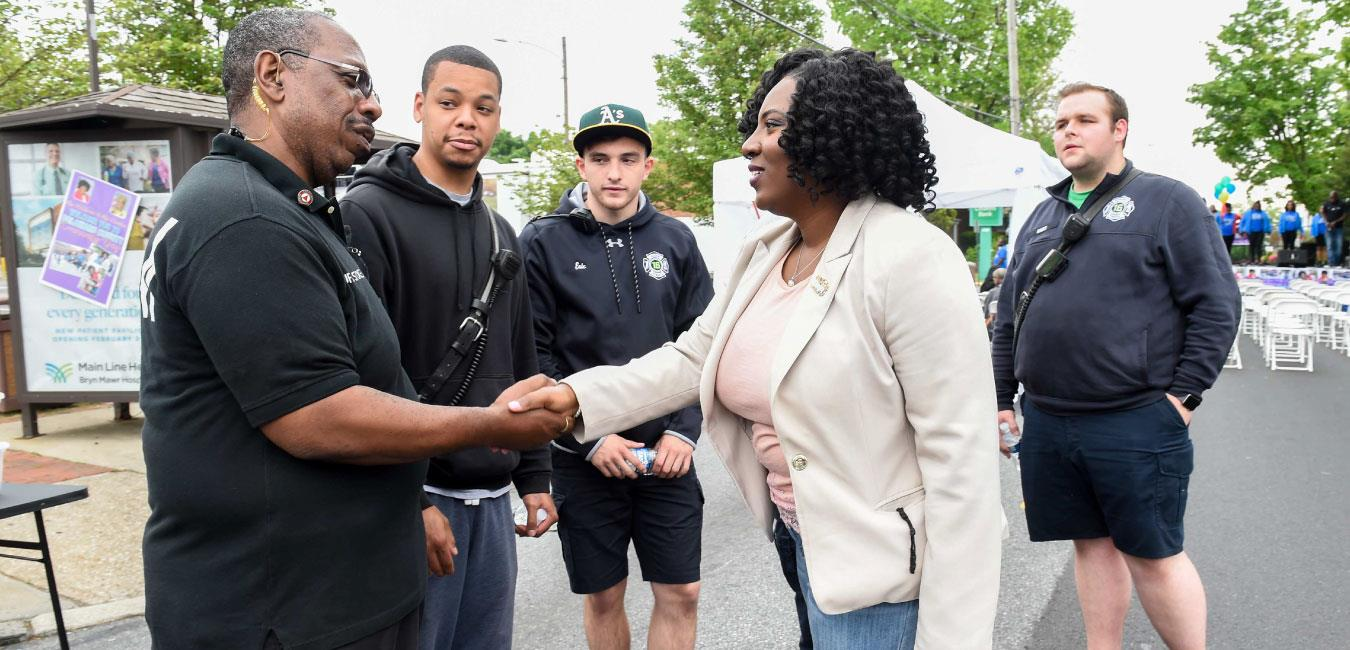 Representative McClinton shaking hands with security officer at outdoor event