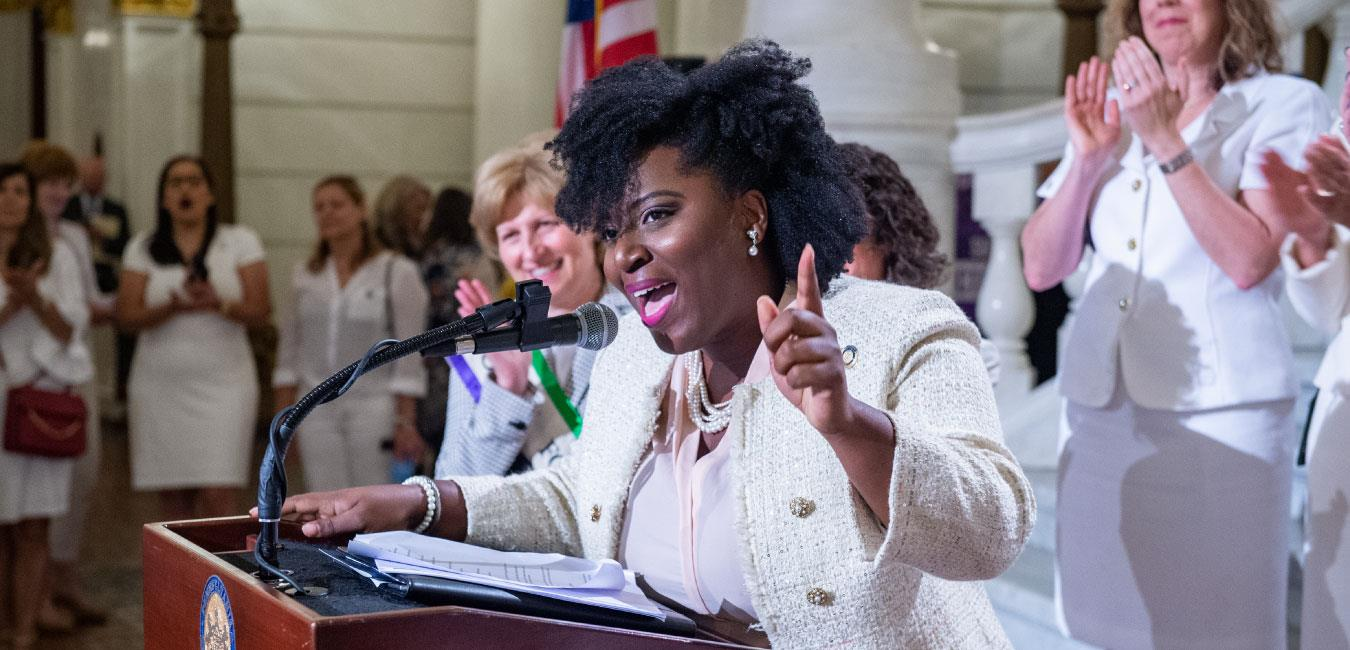 Representative McClinton speaking at podium in front of women wearing white to celebrate women's suffrage in Pennsylvania with finger raised in front of Capitol rotunda steps