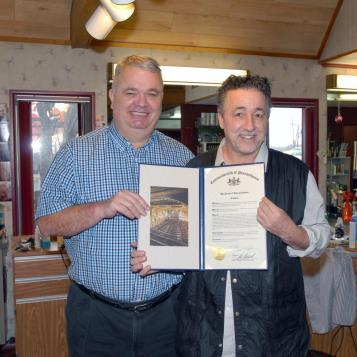 State Rep. Timothy S. Mahoney (left) recently presented Vincent Weaver III with a House citation recognizing his receipt of the Power of Work Award from Goodwill Industries of Southwestern Pennsylvania. A graduate of Uniontown Area Senior High School (1974) and Edinboro University (1979), Weaver opened Vinny's Hair Design in 1983 and overcame substance abuse over two decades ago.