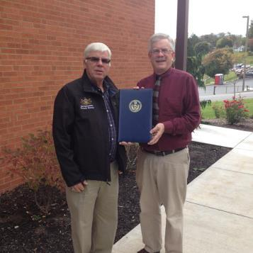 On behalf of Rep. Frank Burns, Charlie Vizzini, a Burns staff member, presents a House citation to Edward Huttenhower from the Small Business Development Center at St. Francis University in recognition of the SBDC's 35th anniversary. The SBDC at St. Francis University is one of 18 SBDCs in the Commonwealth. It works with business owners in Bedford, Blair, Cambria, Fulton, Huntingdon and Somerset counties to help them maintain a competitive edge. The photo is available for download here.
