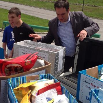Rep. Frank Burns collecting donated pet food items from students at Portage Elementary.