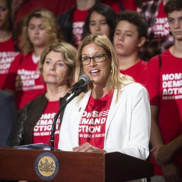 Rep. Melissa Shusterman speaks at a rally with colleagues and members of Moms Demand Action to continue the fight to end gun violence.