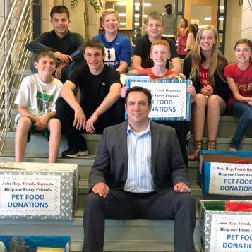 Rep. Frank Burns joins volunteers to raise donations for pet food.