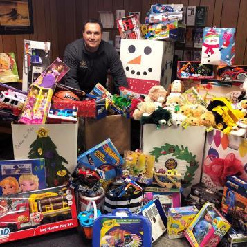 Rep. Frank Burns is pictured with children's toys that his district offices collected for Cuddles For Kids.