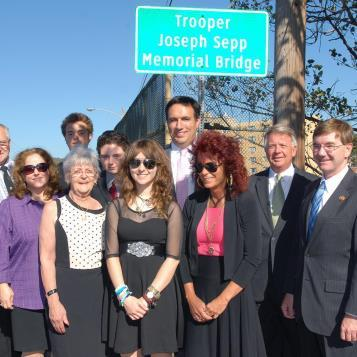 Members of the Sepp family at the unveiling of the new sign for the Trooper Joseph Sepp Memorial Bridge in Windber. From left, Joseph Sepp, Tina Sepp, Joey Sepp, Lana Gay Sepp, Andy Sepp, Amanda Jo Sepp, Rep. Burns, Jenny Sepp, Sen. Wozniak and Congressman Rothfus,
