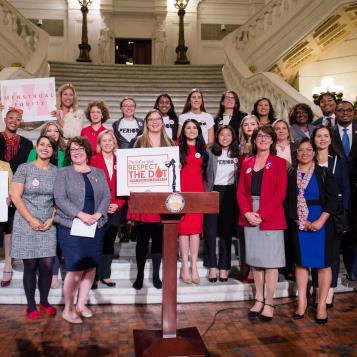 Rep. Mary Isaacson participates in a rally to support legislation that would provide free menstrual products in public schools, universities, and public spaces.
