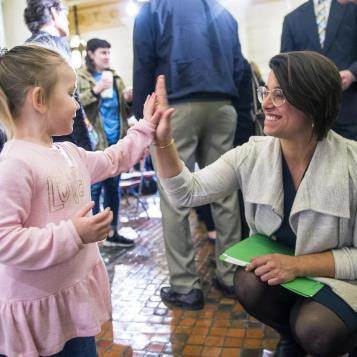 Rep. Sara Innamorato high-fives a child who was in Harrisburg to support an alternative economic vision.