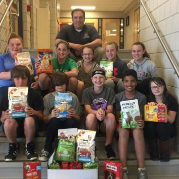 Students pose with their contributions to Rep. Burns' annual Pet Food Drive, before the donations were loaded up for delivery to the Humane Society of Cambria County.