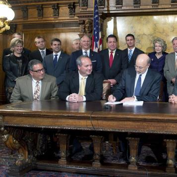 Rep. Paul Costa, the Democratic Chairman of the House Liquor Control Committee, is joined by many of his colleagues, including Democratic Leader Frank Dermody and Democratic Appropriations Chairman Joe Markosek, to watch Gov. Tom Wolf sign a bill modernizing and expanding wine sales in Pennsylvania.