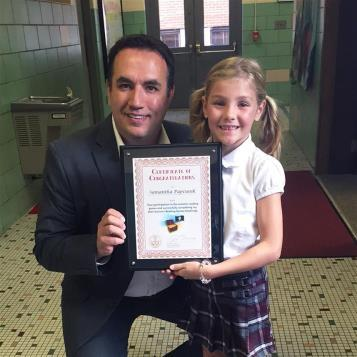 Rep. Frank Burns congratulates Samantha Papcunik for completing a summer reading challenge.